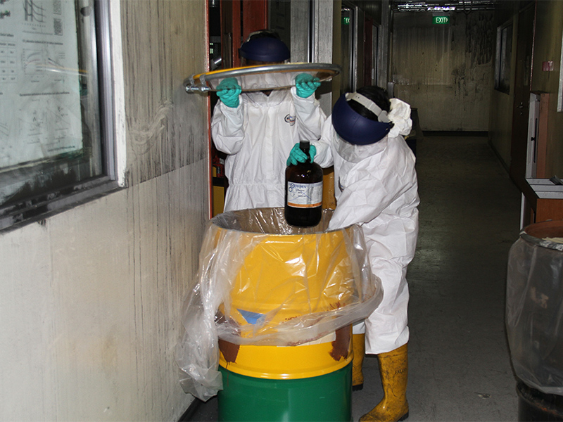 DRS personnel carefully isolate chemical containers for disposal